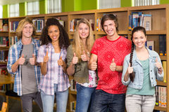Students gesturing thumbs up in library Royalty Free Stock Image
