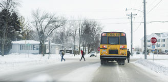 Students getting off school bus during winter. Moorhead, Minnesota, United States - January 11, 2016: Teens being dropped off from classical yellow school bus at stock photography