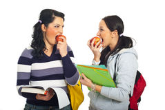 Students girls discuss and eating apples. Two students girls standing face to face having discussion and eating apples isolated on white background Stock Photo