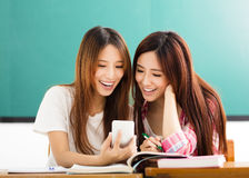 students girls watching the smart phone in classroom Royalty Free Stock Photos