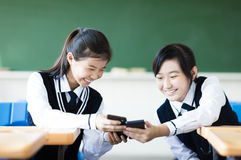 Students girls watching the smart phone in classroom royalty free stock photography