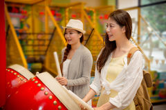 Students going to the amusement park together. Asian chinese female students going to the amusement park together and playing the drum game compete with each Stock Photos