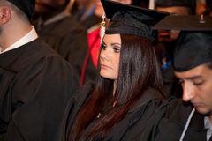 Students on Graduation Day. A woman graduating with a Bachelor's degree from a University listening attentively to the commencement speaker Royalty Free Stock Photo