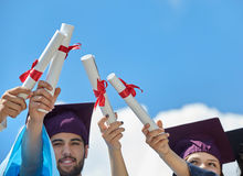 Students graduation day with certificates. Graduates stutents throwing graduation hats in the air royalty free stock photos