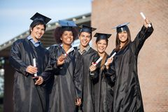 Students In Graduation Gowns Holding Diplomas On Stock Photography