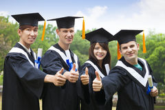 Students in graduation gowns showing diplomas with thumbs Stock Photos