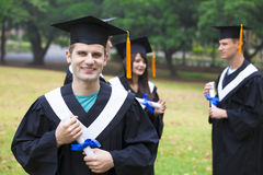 Students in graduation gowns on university campus Royalty Free Stock Photo