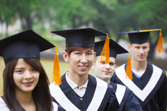 Students in graduation gowns on university campus Royalty Free Stock Images