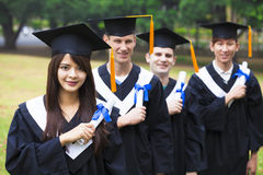 Students in graduation gowns on university campus. Happy students in graduation gowns on university campus Stock Photos