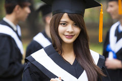 Students in graduation gowns on university campus. Happy students in graduation gowns on university campus Stock Photo