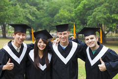 Students in graduation gowns on university campus. Happy students in graduation gowns on university campus Stock Image
