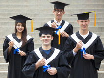 Students in graduation gowns on university campus Royalty Free Stock Photos