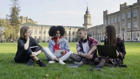 4 Students on the Grass at College Campus with Laptop