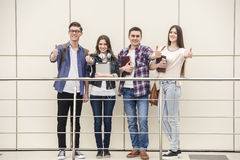 Students. Group of happy young students showing thumbs up in a college. Looking at camera Stock Photos