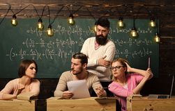 Students, group mates speaking, asking for advice or cheating while teacher watching them. Bearded teacher, lecturer. Professor watching students during test stock photo