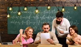 Students, group mates speaking, asking for advice, teacher explains. Bearded teacher, lecturer, professor teaching. Students, chalkboard on background. Studying royalty free stock photos