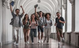 Students in the hall. Beautiful young students are looking at camera and smiling while running through the university hall stock photography