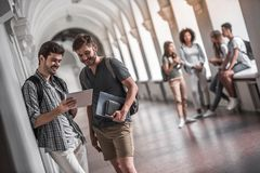 Students in the hall. Beautiful young students are resting in university hall, a guys in the foreground are using a digital tablet and smiling Stock Images