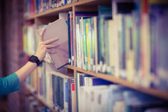 Students hand with smartwatch picking book from bookshelf Royalty Free Stock Images