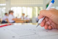 Students hand testing doing examination with pen drawing selected choice on answer sheets in school exams, blur pupils college ba. Ckgroud. Education system stock photography