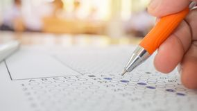 Students hand testing doing examination with pen drawing selected choice on answer sheets in school exams, blur pupils college ba. Ckgroud. Education system royalty free stock image