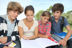 Students with handbooks in school yard Stock Images
