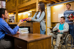 Students with handicapped man at the library counter Stock Image