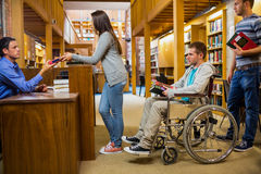 Students with handicapped man in row at library counter Royalty Free Stock Photography