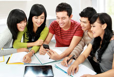 Students with handphone. Group of asian students looking at handphone together Stock Photos
