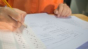 Students hands taking exams, writing examination room with holding pencil on optical form of standardized test with answers and e. Nglish paper sheet on row desk royalty free stock images