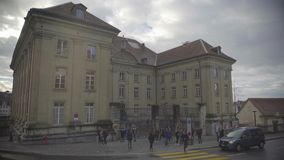Students hanging out near old university building, car  traffic in the street. Stock footage stock video footage