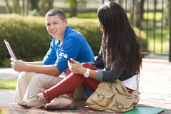 Students hanging out together. Two teenage students, outdoors. One guy and one girl together Royalty Free Stock Photo