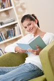 Students - Happy teenager with book on armchair Royalty Free Stock Photo