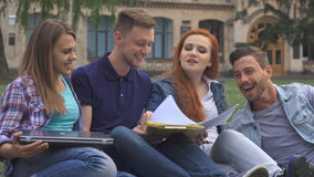 Students have fun on the lawn on campus. Four cute caucasian students having fun on the lawn on campus. Handsome blond guy showing his friends some papers from stock video footage