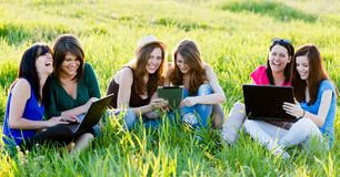 Students Having Fun On Internet. Girlfriends having fun outdoors using wireless internet on their laptops and tablet Stock Photography