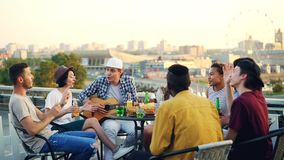 Students are having fun on rooftop playing the guitar, singing and dancing sitting at table on rooftop enjoying free. Time. Modern lifestyle, joy and musical stock video footage
