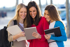 Students having fun with smartphones and tablets after class Royalty Free Stock Image