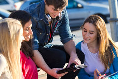 Students having fun with smartphones and tablets after class Royalty Free Stock Photography