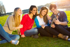 Students having fun with smartphones and tablets after class Royalty Free Stock Photos