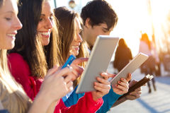 Students Having Fun With Smartphones And Tablets After Class Royalty Free Stock Images