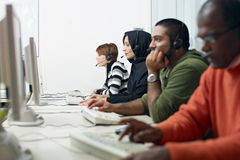 Students with headset in computer lab. Multiethnic computer class with indian, middle eastern, hispanic and caucasian people training with pc. Horizontal shape royalty free stock photos