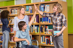 Students high fiving in library Stock Image