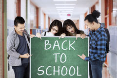 Students hold Back to School text in corridor Royalty Free Stock Photo