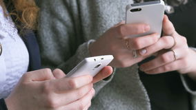 Students hold smart phones in hands indoors. Students dressed in cardigans hold the white smart phones in their hands indoors. Close-up stock video footage