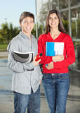 Students Holding Books While Standing In College. Portrait of happy students holding books while standing in college Stock Photography