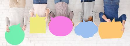 Students holding colorful speech bubbles over white wall stock photography