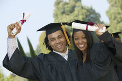 Students Holding Diplomas On Graduation Day. Portrait of happy students holding diplomas on graduation day Stock Photos