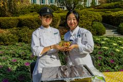 Students holding a dish of pesto pasta. Daejeon, South Korea-November, 8,2017: Two Woosong College SIHOT students holding a dish of pesto pasta at Woojeong royalty free stock photo