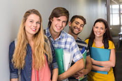 Students holding folders at college corridor. Portrait of happy students holding folders at college corridor Royalty Free Stock Image