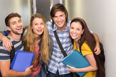 Students holding folders at college corridor. Portrait of happy students holding folders at college corridor Royalty Free Stock Photo